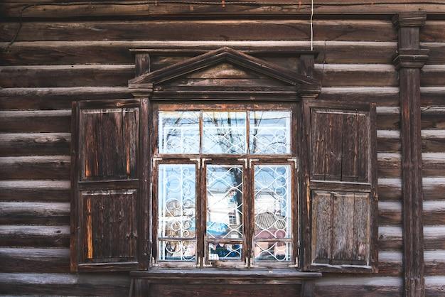 Drewniane okno z okiennicami i rzeźbionymi wzorami na oknach w rustykalnym starym domu