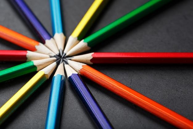 Drewniane ołówki w różnych kolorach w kształcie gwiazdy na czarnym tle.