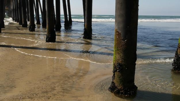 Drewniane pale pod promenadą, molo wybrzeże kalifornii usa. pale, pylony lub filary mostu, plaża