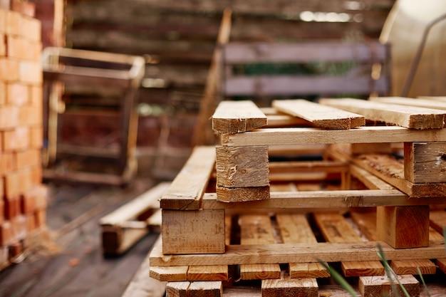 Drewniane palety leżą jedna na drugiej w ogrodzie