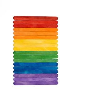 Drewniane patyczki do lodów w kolorze tęczy na białym tle. wielobarwny abstrakcyjna koncepcja lgbt.
