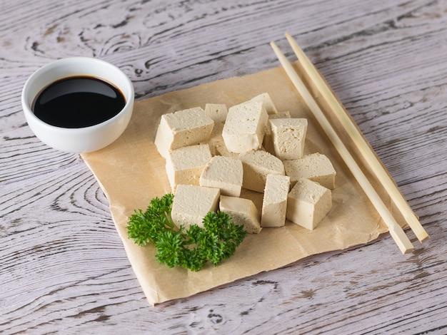 Drewniane patyczki z kawałkami sera tofu i sosem sojowym na drewnianym stole. ser sojowy. produkt wegetariański.