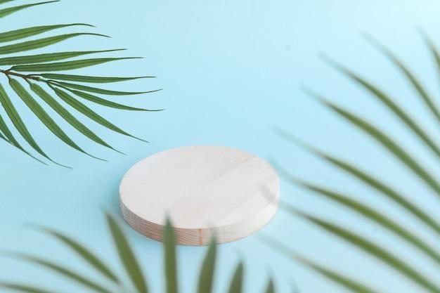 Drewniane podium na produkt kosmetyczny palma pozostawia niebieskie tło