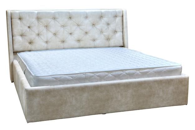 Drewniane podwójne łóżko z kremową ekoskórą i materacami ortopedycznymi.