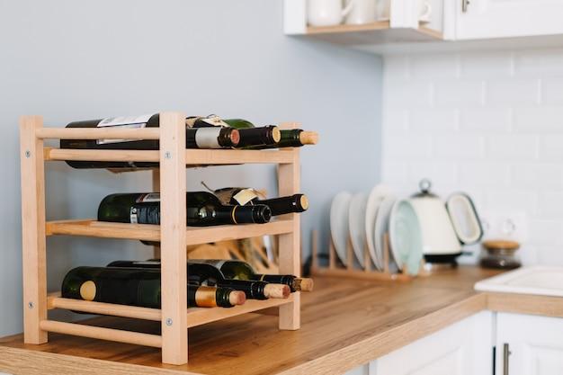 Drewniane półki na wino z butelkami na stole w nowoczesnej kuchni.