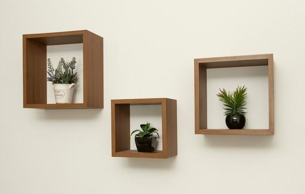 Drewniane półki ścienne z małymi wazonami