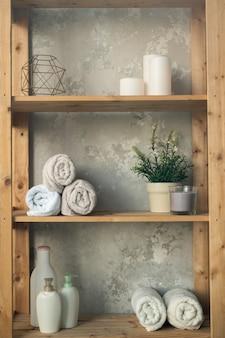 Drewniane półki z rolowanymi ręcznikami, plastikowe słoiki z żelem pod prysznic i mydłem w płynie, zielona roślina w doniczce i świece na szarej ścianie