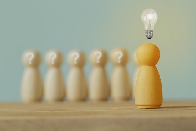 Drewniane postacie człowieka i ludzi stoją z ikoną żarówki i symbolem znaku zapytania. koncepcja kreatywny pomysł i innowacja. zarządzanie zasobami ludzkimi i talentami
