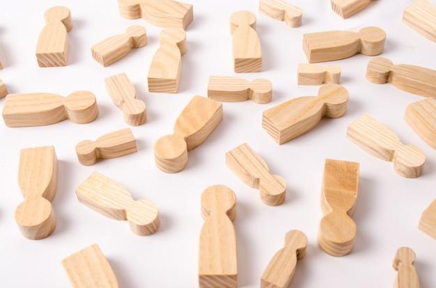 Drewniane postacie ludzi leżą na białym tle.