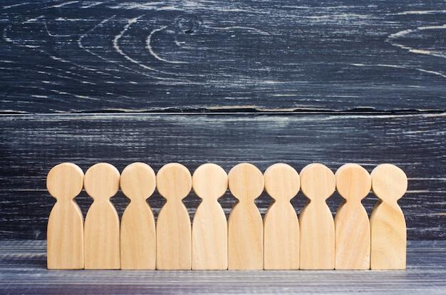 Drewniane postacie ludzi stoją w rzędzie w formacji na tle hebanu.