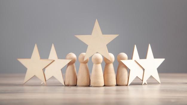 Drewniane postacie ludzkie z gwiazdami. najlepsza ocena i satysfakcja klienta