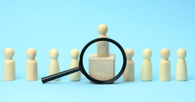 Drewniane postacie mężczyzn stoją na niebieskiej powierzchni i czarnym szkle powiększającym. koncepcja rekrutacji, poszukiwanie utalentowanych i zdolnych pracowników, rozwój kariery, baner
