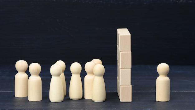 Drewniane postacie mężczyzn tłum stoi przed ścianą z drewnianych klocków, po drugiej stronie jedna postać. pojęcie kłótni i nieporozumienia, duża różnica w ludziach