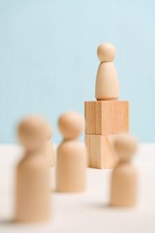 Drewniane postacie z sześcianami na błękitnym tle. koncepcja forum biznesowego i szkolenia. ścieśniać.