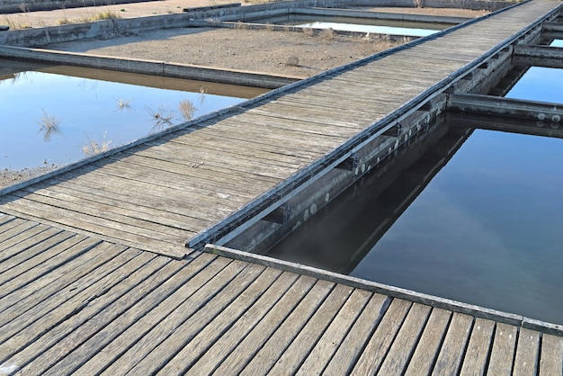 Drewniane przejścia przecinające stare stawy z wodą morską do hodowli ostryg