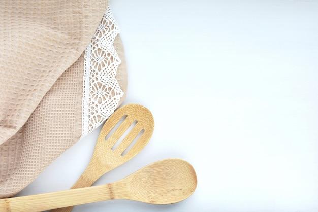 Drewniane przybory kuchenne i ręcznik ze sznurowadłami na białym stole, gotowanie, przepis, menu.