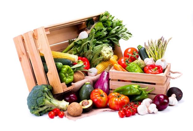 Drewniane pudełka pełne świeżych warzyw na białym tle, idealne do zbilansowanej diety