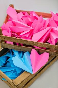 Drewniane pudełka z papierowymi samolotami w kolorze niebieskim i różowym.