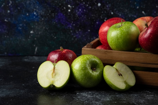 Drewniane pudełko dojrzałych jabłek ekologicznych na czarnej powierzchni. .