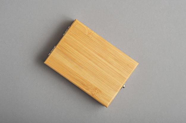 Drewniane pudełko na ostatecznym szarym tle, makieta, miejsce na kopię, układ