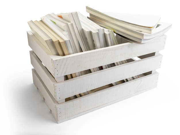 Drewniane pudełko owoców (jabłek) w kolorze białym, pełne czasopism i książek, gotowe do użycia.