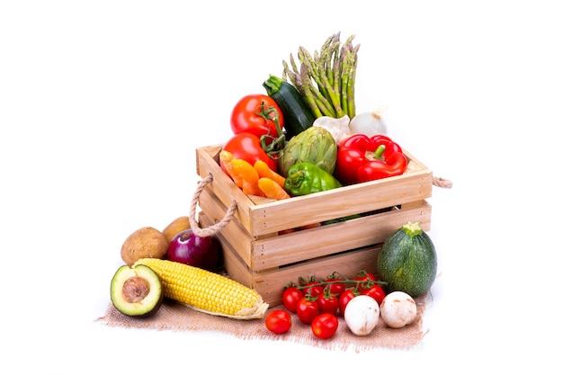 Drewniane pudełko pełne kolorowych i świeżych warzyw dla zrównoważonej i zdrowej diety