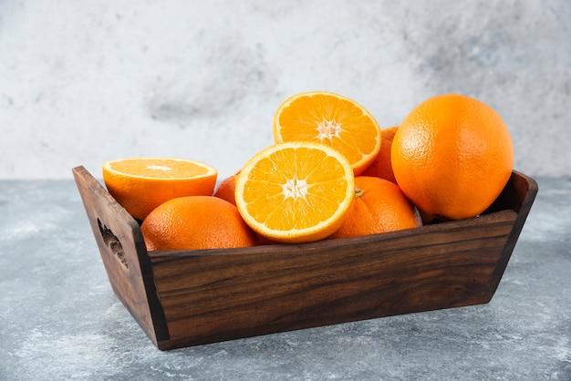 Drewniane pudełko pełne soczystych pomarańczowych owoców pokrojonych w plasterki.