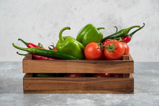 Drewniane pudełko pełne świeżych warzyw na marmurze.