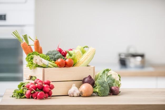 Drewniane pudełko pełne świeżych zdrowych warzyw. brokuły marchew rzodkiewka cebula czosnek kukurydza na drewnianym stole w kuchni.
