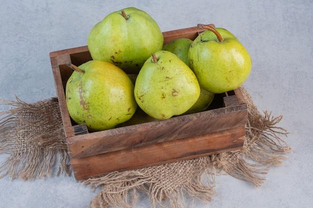 Drewniane pudełko pełne zielonych gruszek.