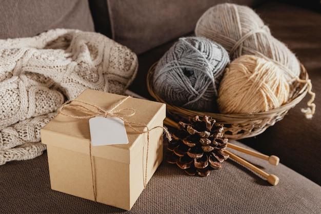Drewniane pudełko pod wysokim kątem z przędzą i szyszkami