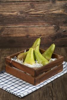 Drewniane pudełko pysznych dojrzałych gruszek na drewnianym tle