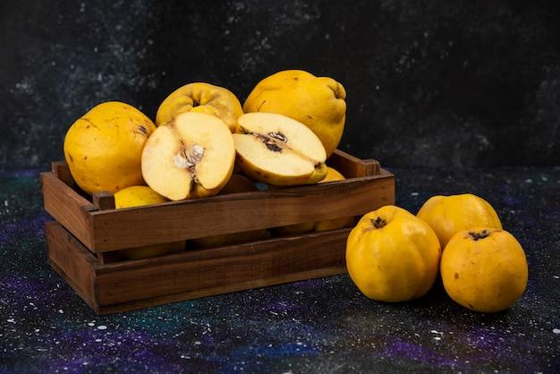 Drewniane pudełko świeżych dojrzałych pigw na ciemnym stole.