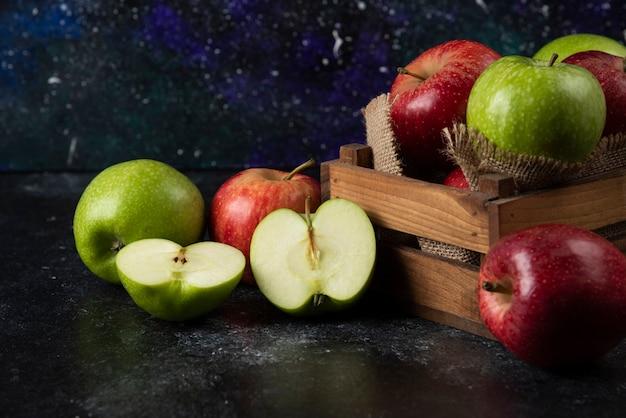 Drewniane pudełko świeżych ekologicznych jabłek na czarnej powierzchni. .