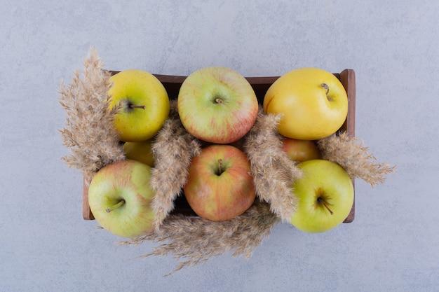 Drewniane pudełko świeżych zielonych jabłek na kamiennym stole.