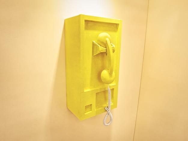 Drewniane pudełko telefoniczne w stylu retro zamontowane na żółtej ścianie