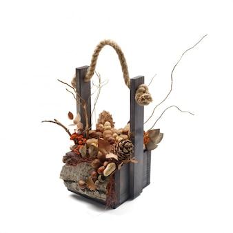 Drewniane pudełko wypełnione gałęziami, suchymi liśćmi, pomarańczowymi jagodami, orzechami i szyszkami jako dekoracyjna kompozycja na białym