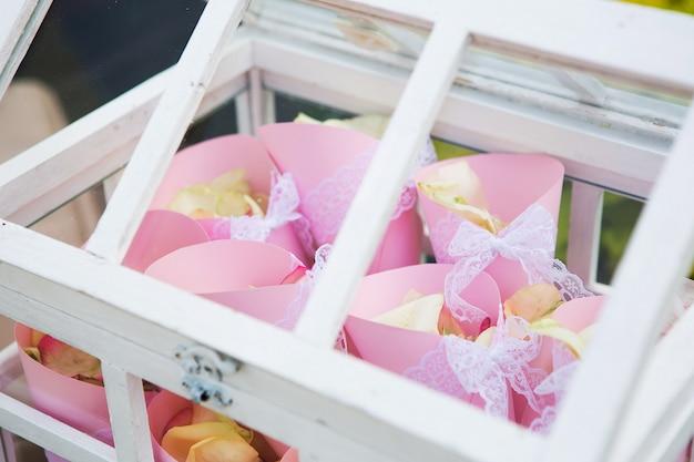 Drewniane pudełko wypełnione płatkami róż na zewnątrz w starożytnym stylu