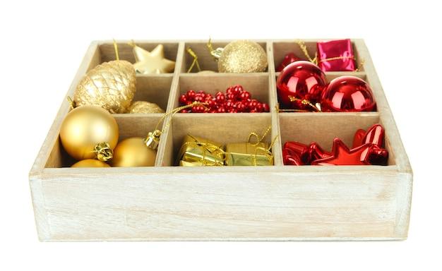 Drewniane pudełko wypełnione świątecznymi dekoracjami, na białym tle