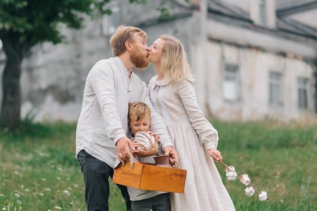 Drewniane pudełko z chlebem, chłopiec gryzie chleb, podczas gdy rodzice całują się. koncepcja szczęśliwej rodziny i naturalnych materiałów