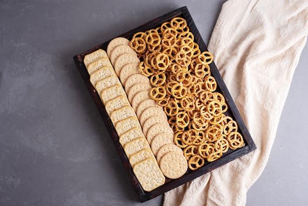 Drewniane pudełko z ciasteczkami, krakersami i mini solonymi precelkami i tekstyliami na szarym betonowym tle, przekąski na imprezę, zbliżenie.