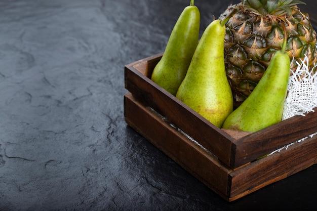 Drewniane pudełko z dojrzałymi ananasami i zielonymi gruszkami na czarnym tle.