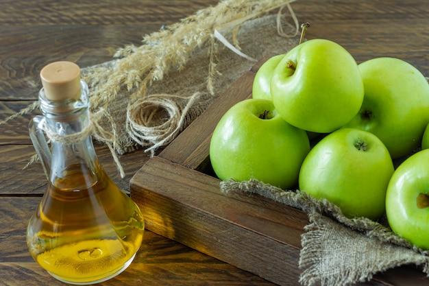 Drewniane pudełko z dojrzałymi zielonymi jabłkami i butelką octu jabłkowego na drewniane tła.