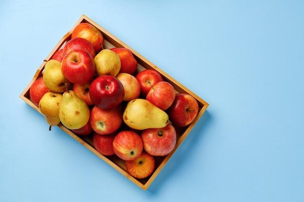 Drewniane pudełko z jabłkami i gruszkami na niebieskim tle