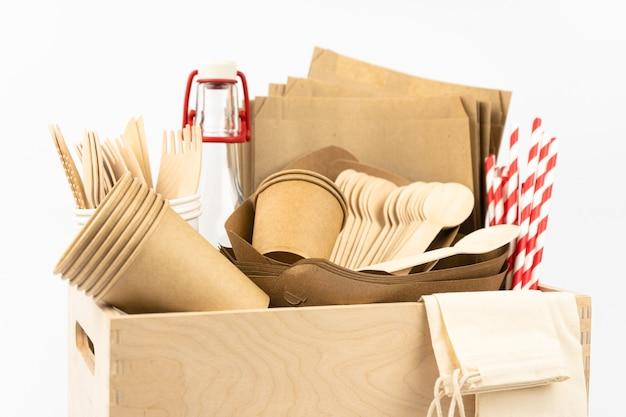 Drewniane pudełko z jednorazowym wykonanym zestawem do dostawy jedzenia lub pikniku kubki, talerze, bambusowe urządzenia