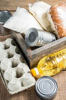 Drewniane pudełko z jedzeniem darowizny, koncepcja pomocy kwarantanny. olej, konserwy, makarony, chleb, cukier, jajko. drewniane tło. widok z góry.