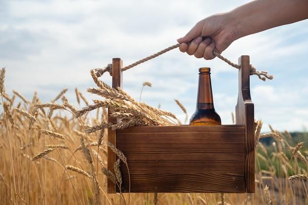 Drewniane pudełko z kłosami pszenicy i szklaną butelką piwa