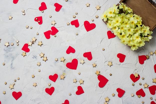 Drewniane pudełko z kwiatami, gwiazdami i czerwonymi sercami.