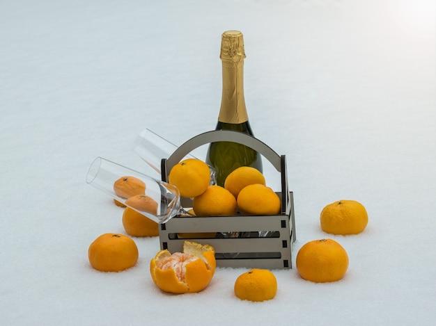 Drewniane pudełko z mandarynkami, kieliszkami i butelką szampana na śniegu.