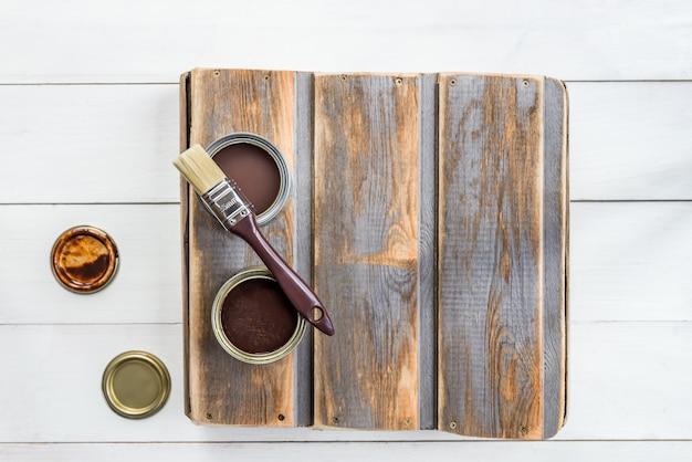 Drewniane pudełko z pędzelkiem i otwartymi puszkami lakieru i bejcy